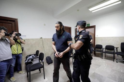 Der Angeklagte in Handschellen auf dem Weg zur Gerichtsverhandlung.