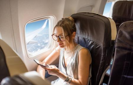 Handynutzerin an Bord eines Flugzeugs.