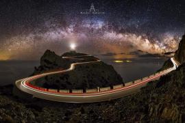 Lichtdurchflutetes Panorama: Die Aufnahme zeigt den Formentor-Leuchtturm unter der Milchstraße und die Lichtspur vorbeifahrender Autos.