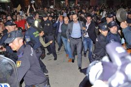 José Ramón Bauzá wird bei der Ausschreitung in Manacor unter Polizeischutz in Sicherheit gebracht.