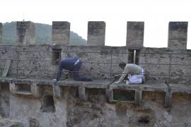 Handwerker bringen das Metallgeländer an der Burgmauer an.