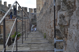 Das Metallgeländer sichert den schmalen Fußweg auf der Burgmauer.