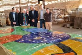 Hoher Besuch im Keramikbetrieb in Campos: Künstler Gustavo (mit buntem Schal) erklärt an einem Teilabschnitt des Mosaikreliefs s