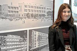 Hoteldirektorin Lola Trian posiert im LobbyWinkel vor den historischen Hotelaufnahmen.