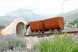 Zwei Loren und ein stilisierter Tunnel auf einem Verkehrskreisel am Ortseingang erinnern an den einstigen Bergbau von Lloseta.