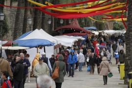 Regenmäntel und -planen prägten den Balearen-Tag  am Passeig Sagrera in Palma de Mallorca.
