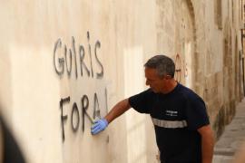 Ein Arbeiter entfernt ein touristenfeindliches Grafitti an einer Hauswand in Palma.