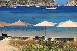 Edle Sonnenschirme und Liegen an der Strandbucht im Meeres-Nationalpark Cabrera südlich von Mallorca.