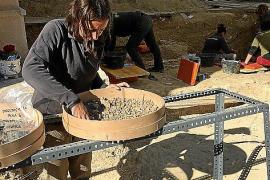 Eine Mitarbeiterin siebt den Aushub durch, um auch kleinste Knochen zu bergen.