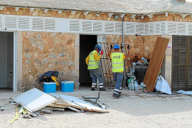 Arbeiter transportieren an einer der Strandbuden am Es-Trenc-Strand erste Gebäudeteile ab.