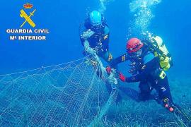Polizeitaucher ziehen zurückgelassenes Fischernetz aus dem Meer