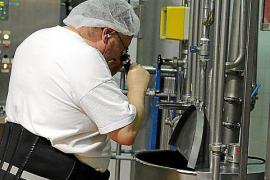 Mit einem Refraktor, einem Gerät zur Bestimmung des Zuckergehalts in Flüssigkeiten, überprüft ein Mitarbeiter einen Produktionsv