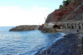 """Die winzige Strandbucht mit den roten Felsen aus Buntsandstein beherbergt die traditionellen Bootsschuppen """"Escars"""". Der Berghan"""