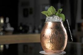 """Der """"Moscow Mule"""" kommt stilecht im Messingbecher und besteht aus Wodka, frischem Ingwer oder Ginger Ale, frischer Gurke und einem Ingwerbier mit einer würzigen Note. Dazu Crushed Ice und das typische Melissenblatt als Garnitur."""