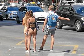 Touristin schlendert mit Bikini über Palmas Plaça d'Espanya
